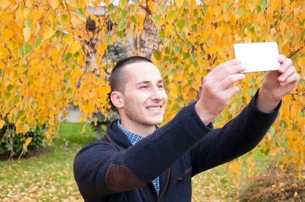 Jugendlicher mit einem intelligenten telefon park öffentlich sich fotografierend
