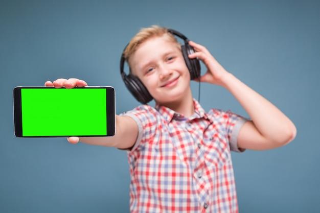 Jugendlicher mit kopfhörern zeigt smartphoneanzeige