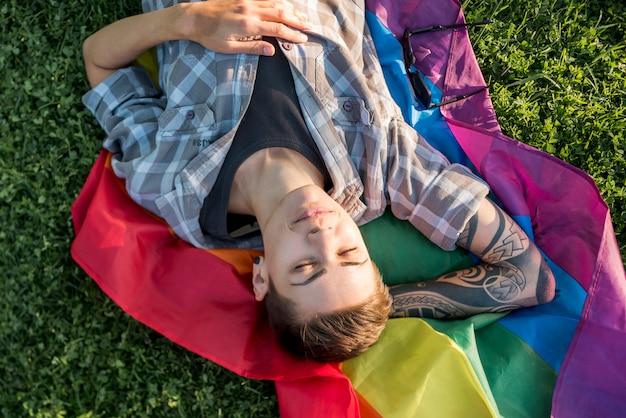 Jugendlicher mit kurzen haaren auf lgbt-flagge