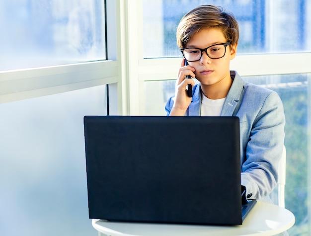 Jugendlicher netter geschäftsjunge mit telefon und computer im büro