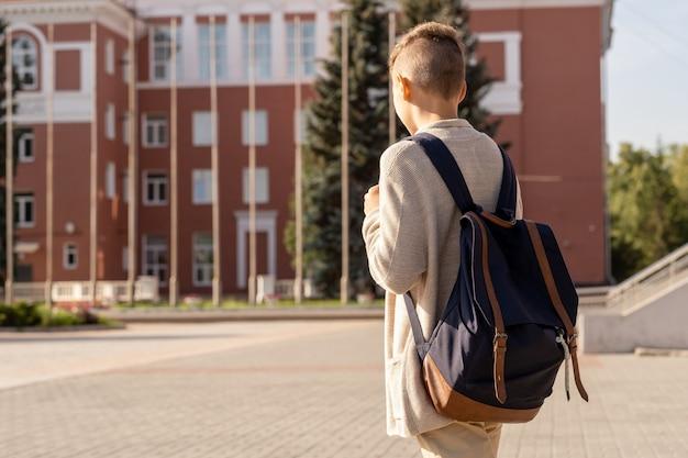 Jugendlicher schuljunge mit schwarzem rucksack, der zur schule zieht