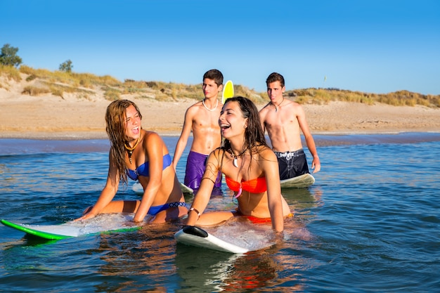 Jugendlichersurfjungen und -mädchen, die ove surfbrett schwimmen