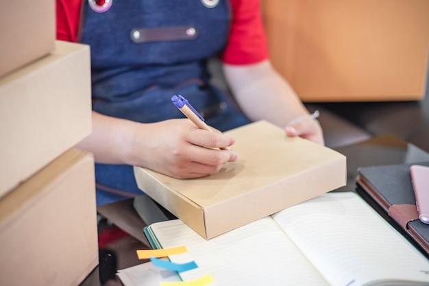 Jugendliches asiatisches mädchen bereiten lieferungskästen zu hause für on-line-maketing verkäufe vor. junge unternehmer oder freiberufliche mädchen starten kleinunternehmen mit etwas online zu verkaufen.
