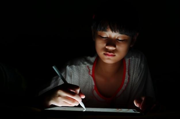 Jugendliches asiatisches mädchen, das tablettenzeichnung beim lügen auf bett verwendet