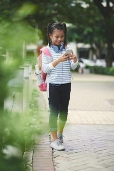 Jugendliches asiatisches schulmädchen mit dem rucksack, der im park steht und smartphone überprüft
