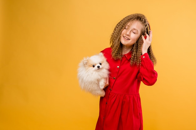 Jugendliches mädchen, das einen kleinen hund in ihren händen hält