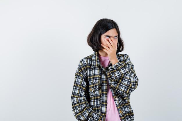 Jugendliches mädchen, das mit der hand auf dem mund im hemd, in der jacke gähnt und schläfrig aussieht, vorderansicht.