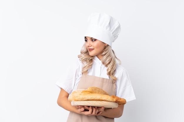 Jugendlichfrau in der chefuniform. weiblicher bäcker, der eine tabelle mit einigen broten über dem lokalisierten weiß schaut zur seite hält