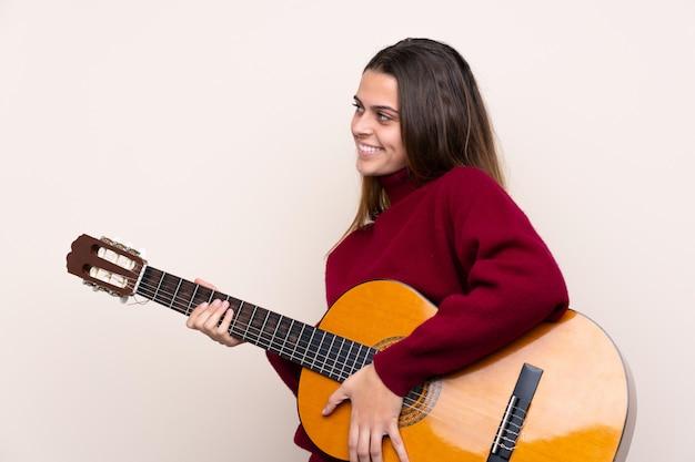 Jugendlichfrau mit gitarre über der lokalisierten wand, die seite schaut
