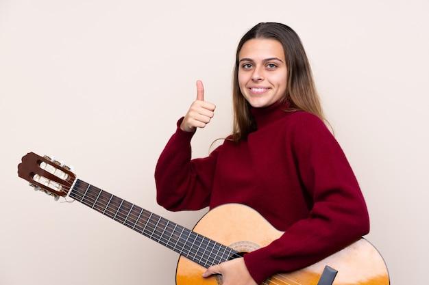 Jugendlichfrau mit gitarre über lokalisierter wand mit den daumen oben, weil etwas gutes geschehen ist