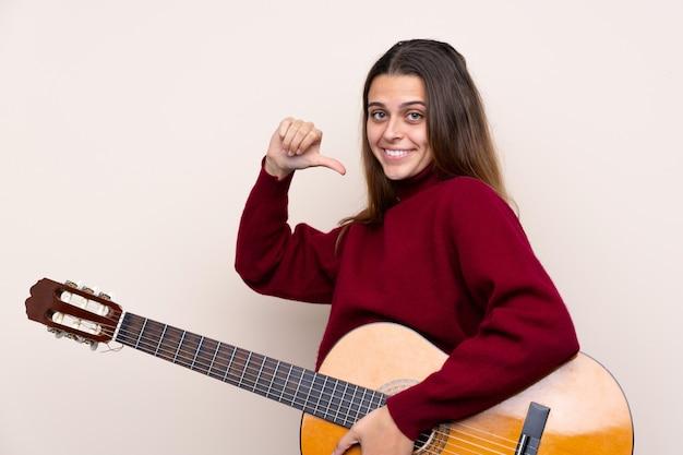 Jugendlichfrau mit gitarre über lokalisierter wand stolz und selbstzufrieden