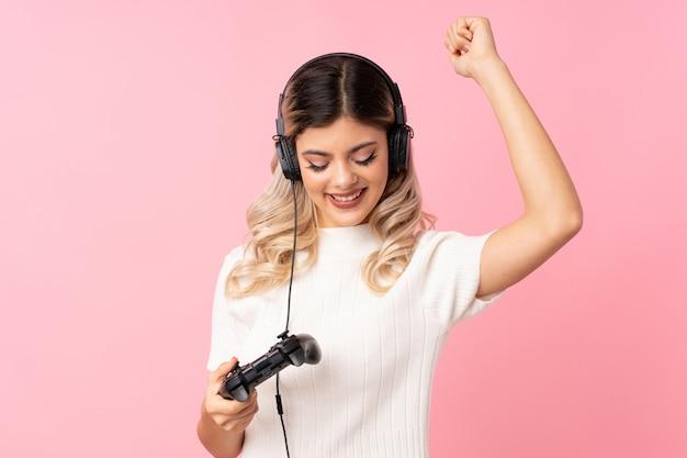 Jugendlichfrau über dem lokalisierten rosa, das an den videospielen spielt