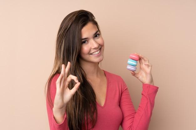 Jugendlichfrau über der lokalisierten wand, die bunte französische macarons hält und okayzeichen mit den fingern zeigt