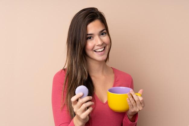 Jugendlichfrau über der lokalisierten wand, die bunte französische macarons und eine schale milch hält