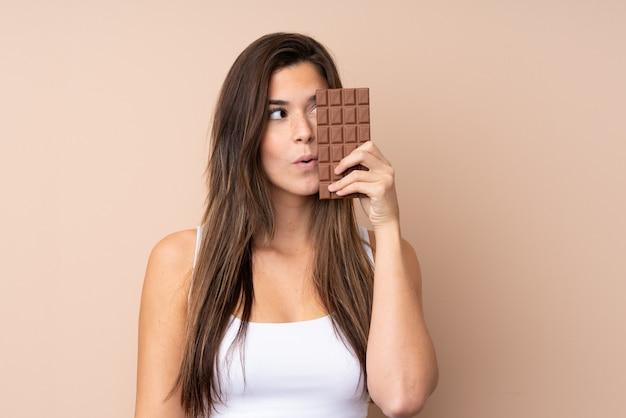 Jugendlichfrau über der lokalisierten wand eine schokoladentablette nehmend und überrascht