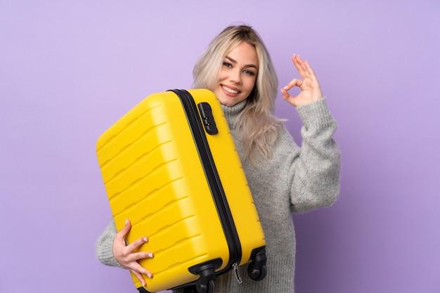 Jugendlichfrau über lokalisierter purpurroter wand in den ferien mit reisekoffer und herstellung des okayzeichens