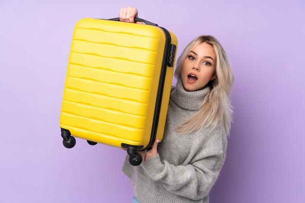 Jugendlichfrau über lokalisierter purpurroter wand in den ferien mit reisekoffer