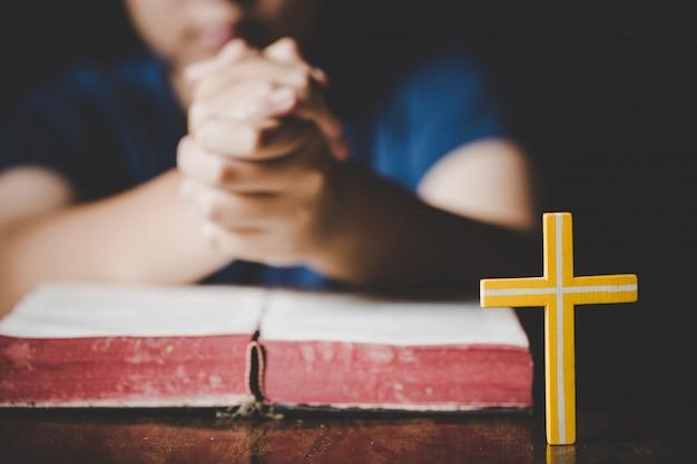 Jugendlichfrauenhand mit dem kreuz und bibel, die, hände beten, faltete sich im gebet auf einer heiligen bibel