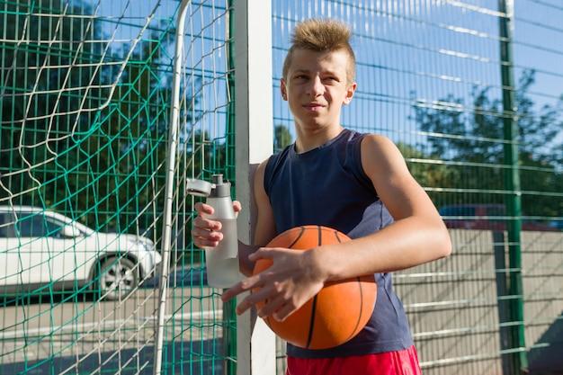 Jugendlichjunge, der basketball mit ball spielt