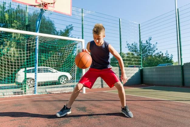 Jugendlichjunge, der basketballspieler spielt