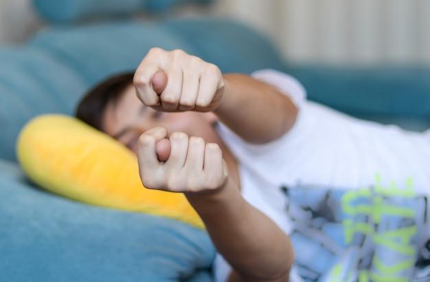 Jugendlichjunge, der zu hause auf dem sofa zeigt feige liegt