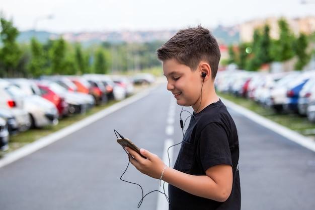 Jugendlichjunge in der zufälligen kleidung hörend musik an seinem handy.