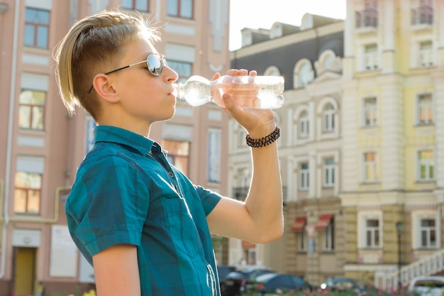 Jugendlichjunge trinkt wasser von der flasche