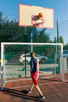 Jugendlichjungen-straßenbasketballspieler