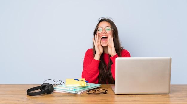 Jugendlichkursteilnehmermädchen, das in einer tabelle schreit und etwas ankündigt studiert