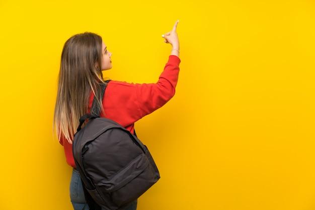 Jugendlichkursteilnehmermädchen, das zurück mit dem zeigefinger zeigt