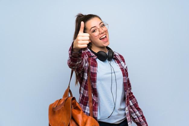 Jugendlichkursteilnehmermädchen über getrennter blauer wand mit den daumen oben, weil etwas gutes geschehen ist