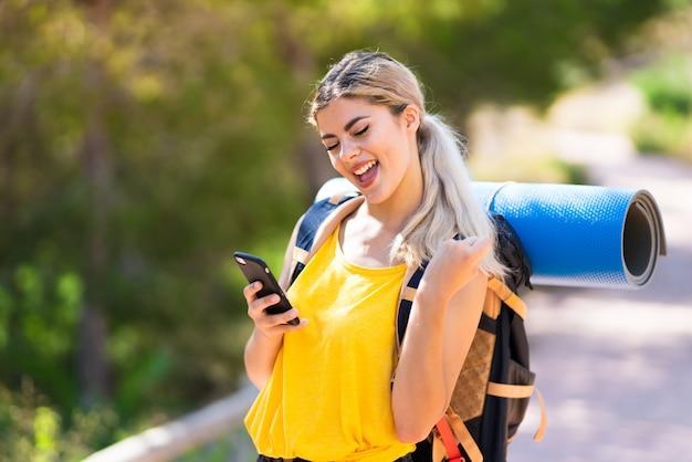 Jugendlichmädchen, das am freien mit telefon in siegposition wandert