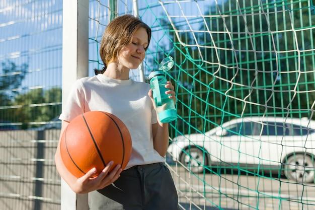 Jugendlichmädchen, das basketball mit ball spielt