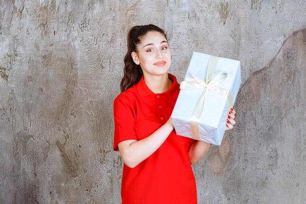 Jugendlichmädchen, das eine blaue geschenkbox mit weißem band umwickelt hält.