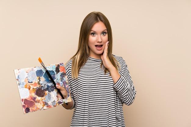 Jugendlichmädchen, das eine palette über getrenntem hintergrund mit überraschungsgesichtsausdruck anhält