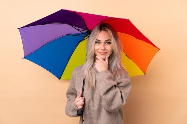 Jugendlichmädchen, das einen regenschirm über dem wandlachen hält