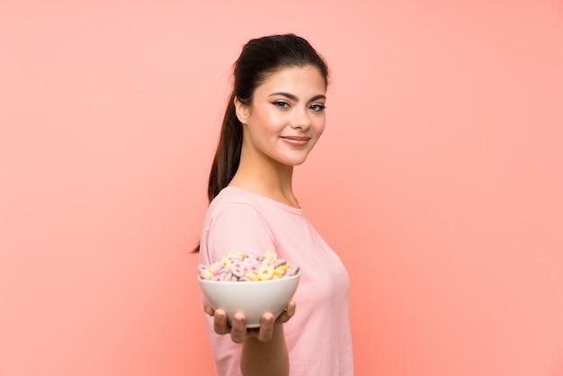 Jugendlichmädchen, das frühstückskost aus getreide über lokalisierter rosa wand isst