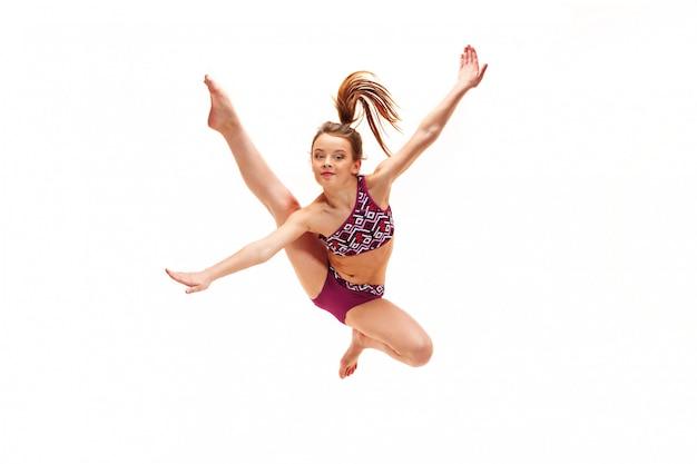 Jugendlichmädchen, das gymnastikübungen auf weiß tut