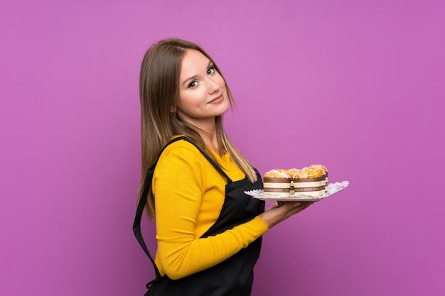 Jugendlichmädchen, das viele verschiedene minikuchen über lokalisiertem purpurrotem hintergrund hält