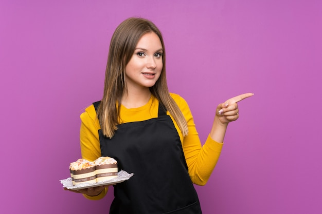 Jugendlichmädchen, das viele verschiedene minikuchen über lokalisiertem purpurrotem hintergrund überrascht hält und finger auf die seite zeigt