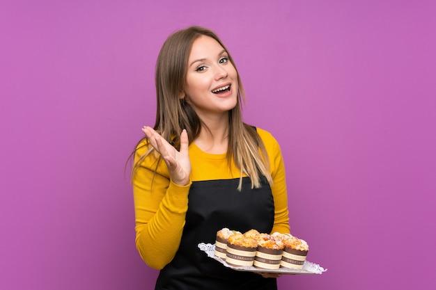 Jugendlichmädchen, das viele verschiedene minikuchen über lokalisiertem purpurrotem hintergrund unglücklich und mit etwas frustriert hält