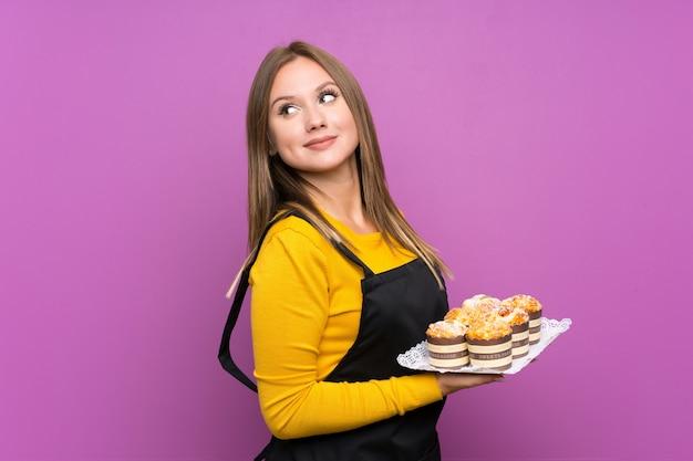 Jugendlichmädchen, das viele verschiedene minikuchen über lokalisiertem purpurrotem lachen hält