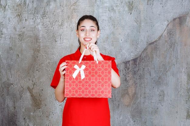 Jugendlichmädchen im roten hemd, das eine rote einkaufstasche hält.