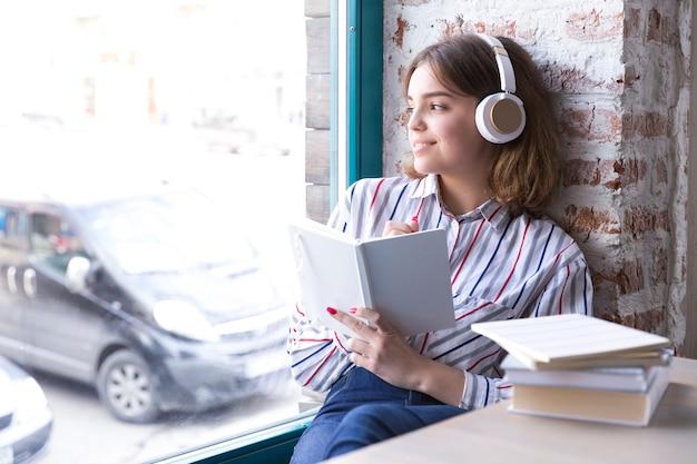 Jugendlichmädchen in den kopfhörern, die mit dem offenen buch heraus schaut fenster sitzen