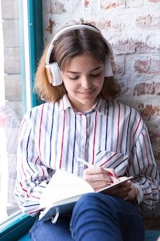 Jugendlichmädchen in den kopfhörern, die mit offenem notizbuch sitzen und eigenhändig schreiben