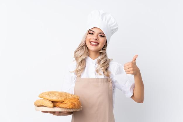 Jugendlichmädchen in der chefuniform. der weibliche bäcker, der eine tabelle mit einigen broten über dem lokalisierten weiß gibt daumen hält, up geste