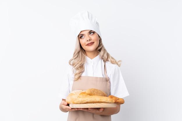 Jugendlichmädchen in der chefuniform. weiblicher bäcker, der eine tabelle mit einigen broten über lokalisiertem weißem hintergrund oben lacht und schaut hält
