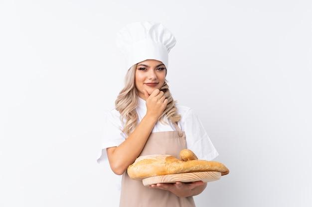 Jugendlichmädchen in der chefuniform. weiblicher bäcker, der eine tabelle mit einigen broten über lokalisiertem weißem hintergrundlachen hält
