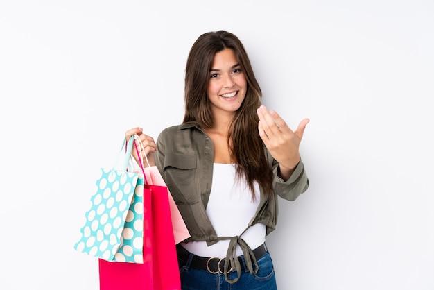 Jugendlichmädchen mit der einkaufstasche, die einlädt, mit der hand zu kommen. schön, dass sie gekommen sind