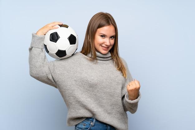 Jugendlichmädchen mit der strickjacke, die eine fußballkugel anhält